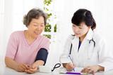 nurse checking senior woman blood pressure