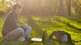 man  student victory surprise joy with laptop notebook sitting on green grass lifestyle lawn sunlight