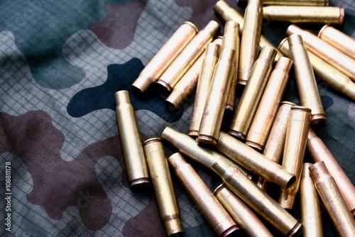 Stare łuski po nabojach na tle kamuflażu wojskowego