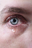close up of blue eye of man crying in tears sad and full of pain in depression