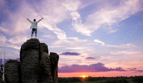 Winner man standing on the top of mountain panoramic view
