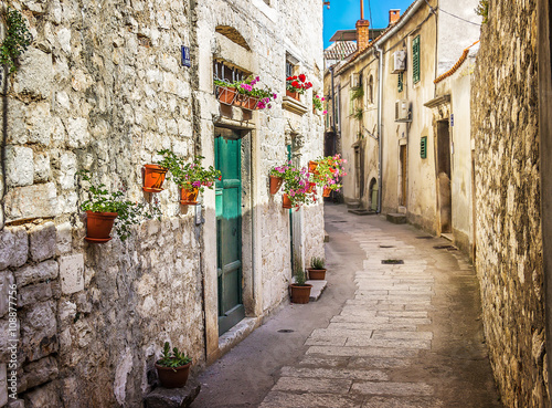 Narrow old street and yard in Sibenik city, Croatia, medieval zone