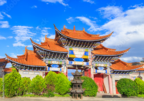 Poster Arched  entrance of Chinese temple under blue sky and white clou