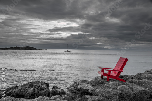 Red chair contrasting with black and white ocean background.