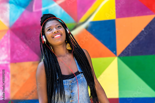 Afro woman listing to music on colorful background Poster