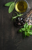 Greek black olives, fresh herbs and oil on dark rustic wooden background.