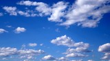 Natural background - white clouds running. Blue clear sky. Spring sunny day.
