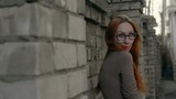 beautiful girl with red hair  wearing glasses standing near brick wall and barbed wire close up
