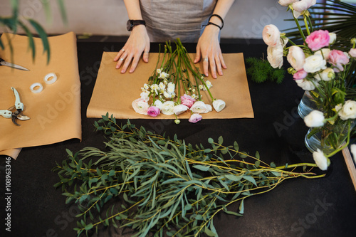 Female florist designing and creating flower bouquet on black table