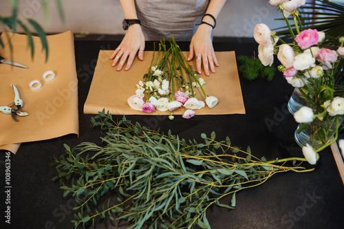Zdjęcia na płótnie, fototapety, obrazy : Female florist designing and creating flower bouquet on black table