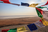 Tibetan Buddhist prayerful flags on the wind  and the desert landscape of the salt plain from Bogdo hill. A hot summer evening