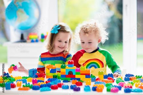 Leinwanddruck Bild Kids playing with colorful plastic blocks