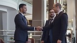 Two businessmen discussing something in hotel lobby, their partner coming and shaking their hands. One man introducing him to their colleague and smiling
