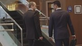 Rear view of two businessmen walking together in business center and going upstairs