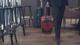 Tilt up of businesswoman and businessman walking with suitcases in hotel lobby