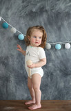 Little baby girl with a wooden spoon on the background of black bord