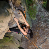 Portrait of young sporty fit woman is climbing the big natural rock with rope in summer time. Top view. Accent on hands. Healthy lifestyle concept. 1x1