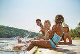 Fototapety Familie am See hält Füße ins Wasser