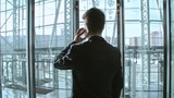 Rear view of businessman standing in modern glass elevator and talking on the phone