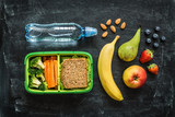 Fototapety School lunch box with sandwich, vegetables, water and fruits