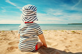 Fototapety Little baby boy sitting on the beach in summer day