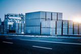 stacked cargo containers at harbor against sunbeam,blue toned image. - 109135397