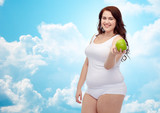 happy plus size woman in underwear with apple