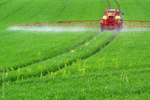 Poster Traktor mit Feldspritze beim Ausbringen von Pflanzenschutzmittel