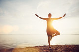 Young woman standing in yoga pose on the beach and meeting sunrise. Intentional sun glare, lens flare effect - 109149526