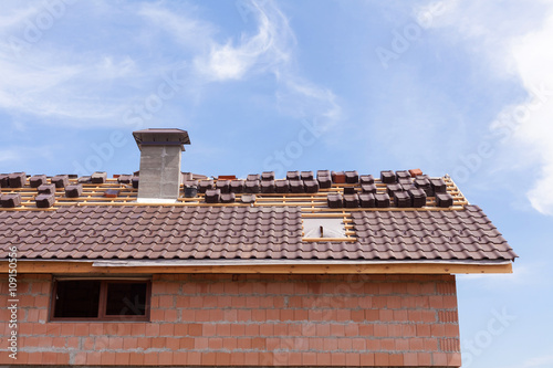 Staande foto Industrial geb. A roof with chimney under construction with stacks of roof tiles ready to fasten