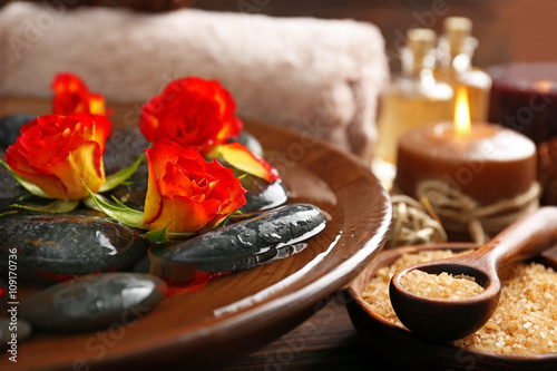 Spa wooden bowl with water, flowers and stones closeup © Africa Studio