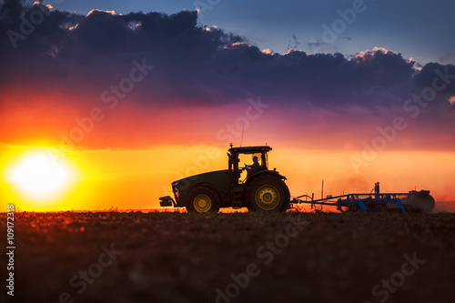 Plagát Farmer in tractor preparing land with seedbed cultivator