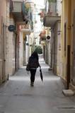 Signora a passeggio con borsetta e ombrello