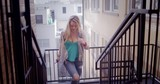Attractive young blonde woman walks up fire escape