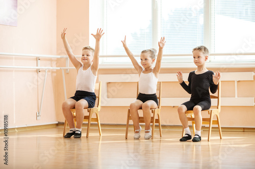 Young dancers playing or doing exercise while sitting on chairs at ballet class  © Andrey Bandurenko