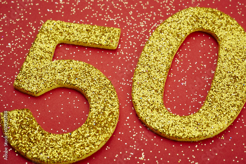 Poster Number fifty golden color over a red background. Anniversary