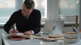 Tilt up of businessman sitting at his office table and working with documents