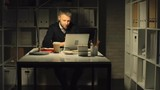 Businessman sitting in the dark office and reading good news on his laptop; he clapping his hands and yelling
