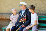 WWII veteran with children. Grandchildren looking at grandfather