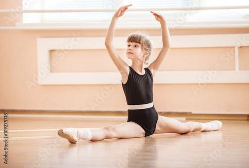 Young girl doing splits while warming up at ballet dance class © Andrey Bandurenko
