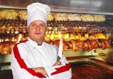 cuoco con coltello davanti ai pollo allo spiedo