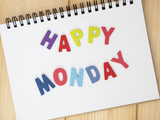 "Word spelling ""Happy Monday"" on notebook page with wood background (Business concept)"