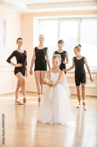 Little girl holding pointe shoes, older ballet danding students in the background © Andrey Bandurenko