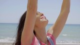 Side view of grinning young woman in long brown hair and pink top with arms extended up near ocean beach horizon