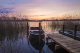 łódka zacumowana do drewnianego pomostu nad jeziorem