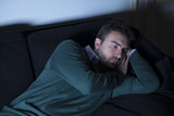 Man depressed thinking lying on the couch