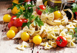 Farfalle pasta, parsley and spices, red and yellow cherry tomato