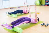 Fit women doing workout, yoga pilates back bend exercise at fitness club