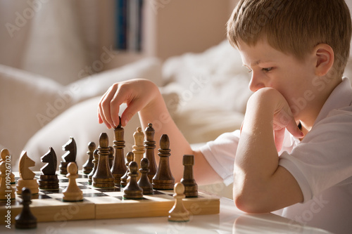 Fotografiet Boy playing chess in the room