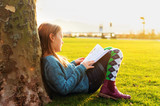 Adorable little girl reading book in the park at sunset